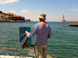 man in white and blue striped long sleeved shirt painting near seashore